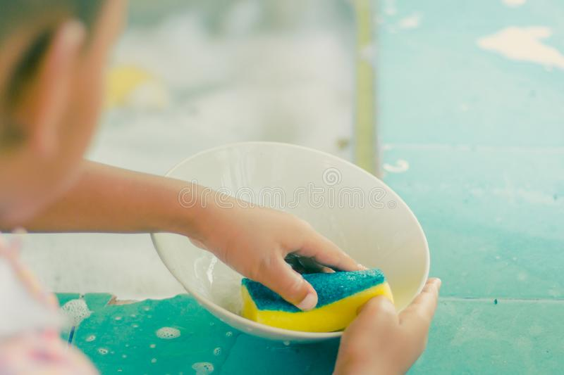 Close up to hands of Kindergarten student is cleaning dish. stock photos