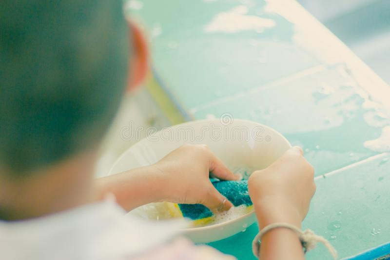 Close up to hands of Kindergarten student is cleaning dish. stock image