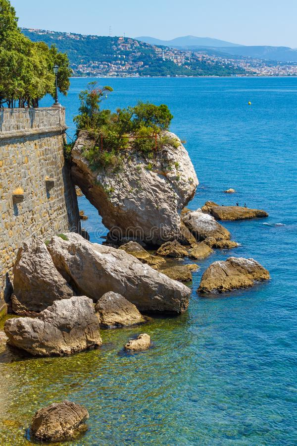 Close up to stone wall are big rocks in the sea. In the blue sea water of Adriatic sea are big stones, touched a wall of stock photo