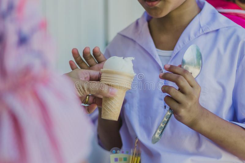 Close-up to Teacher `s hands give ice cream to students. stock photos