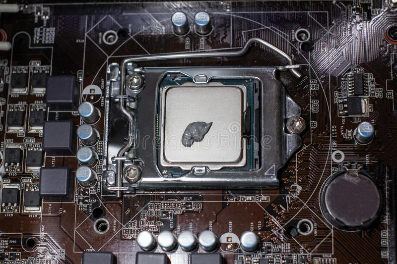 Close up to the thermal paste compound on the top of cpu in the socket. Concept of repairing or upgrading computer hardware royalty free stock photos