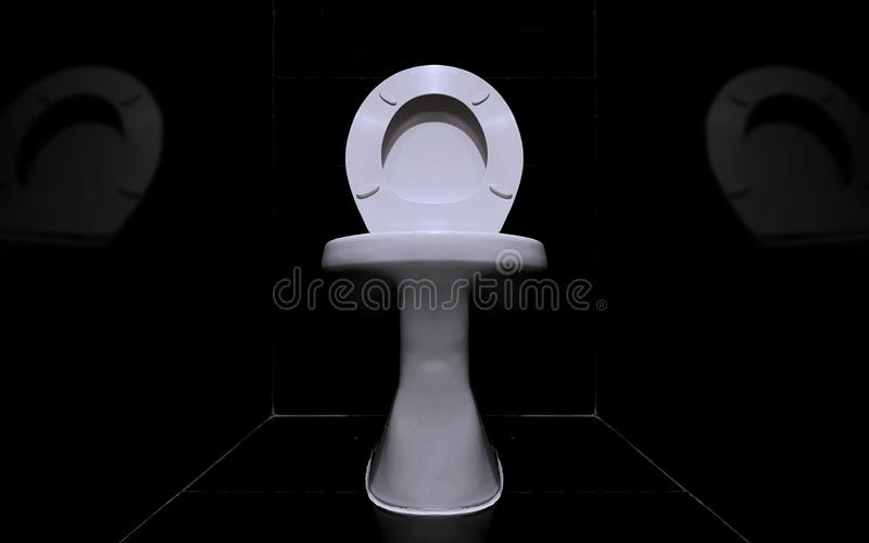Close up to a white sanitary ware in a dark toilet room. With blur reflect stock photos