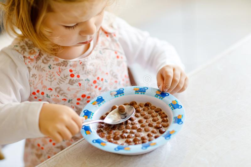 Close up of toddler girl eating healthy cereal with milk for breakfast. Cute happy baby child in colorful clothes stock photos