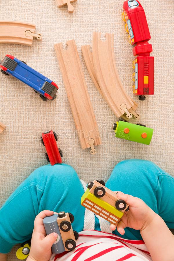 Close-up of toddler`s hands playing with railroad and colorful trains. Indoors. Early learning and development royalty free stock photography
