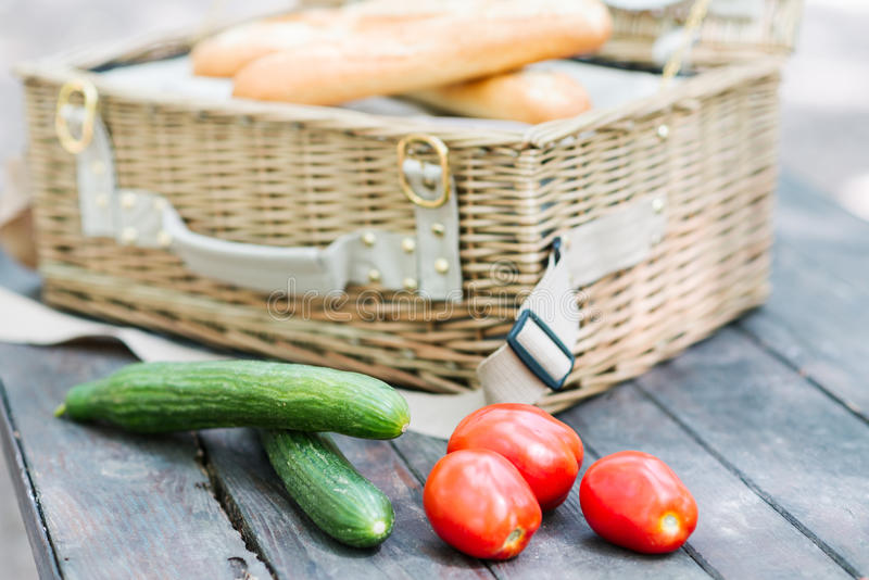 Close up of tomatoes and cucumbers over wooden table in front of an open picnic basket. Close up of tomatoes and cucumbers over wooden table in front of an open stock photo