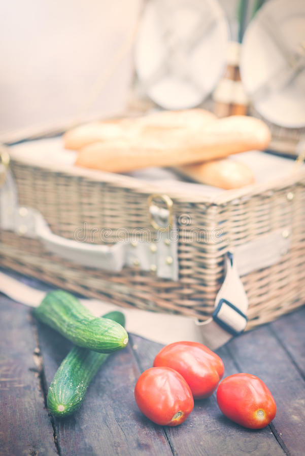 Close up of tomatoes and cucumbers over wooden table in front of an open picnic basket. Vintage style. Close up of tomatoes and cucumbers over wooden table in stock images
