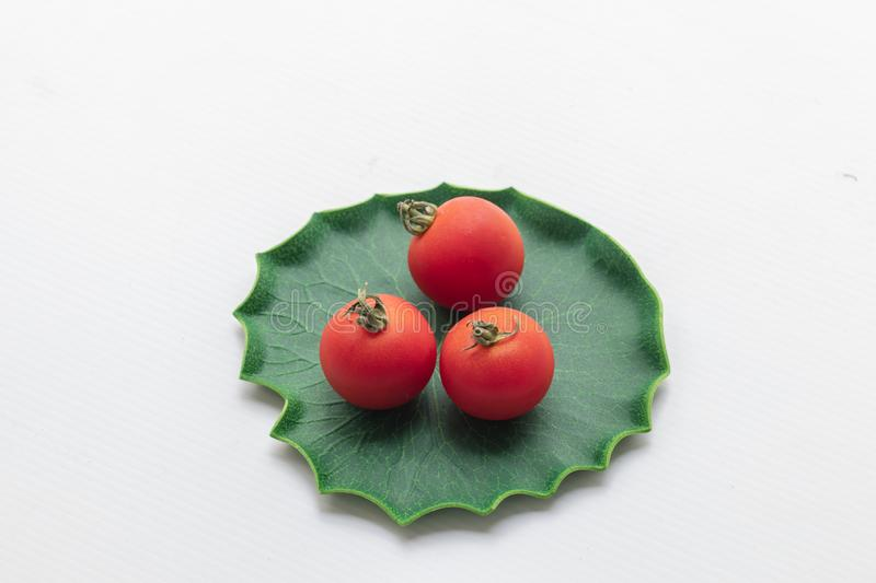 Close up tomatoes in green leaf on isolate white background.Selective focus red tomatoes. royalty free stock image