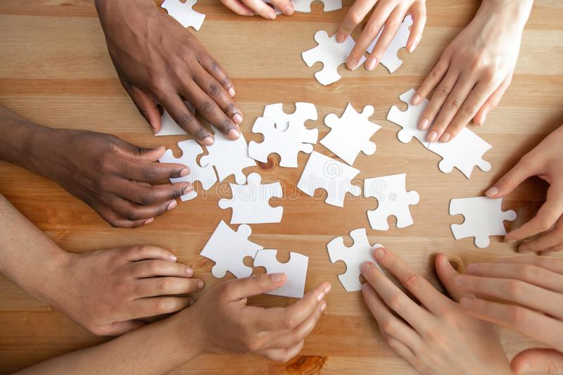 Close up top above view diverse hands assembling puzzles. royalty free stock photo