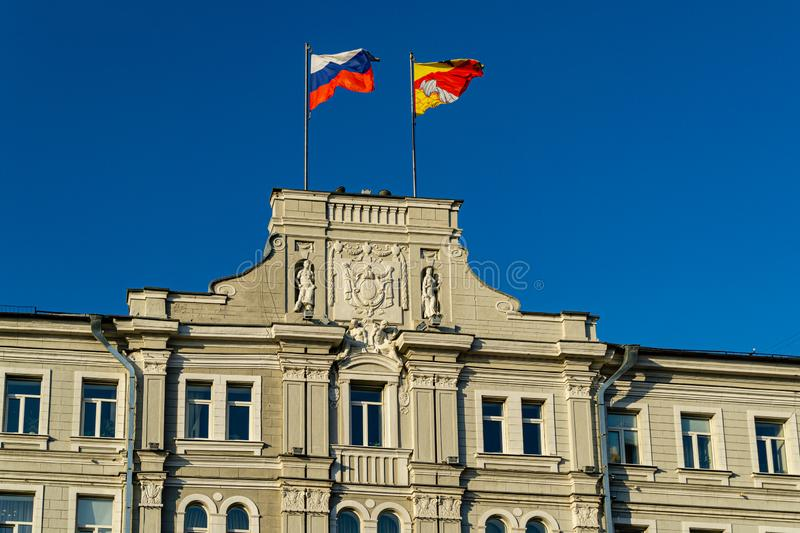 Close-up of top decoration of main facade Voronezh city administration building on Plekhanovskaya Street 10. Building was built in 1914-1915. Flags of Russia royalty free stock image