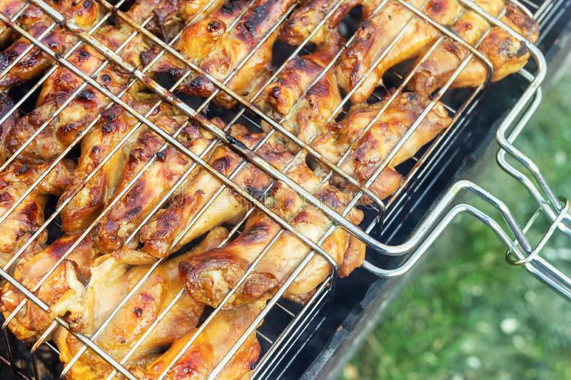 Close-up top view chicken wings cooking in metal barbecue grid on grill brazier. Outdoors weekend party on backyard. Tasty golden. Brown delicious bbq meal food stock images