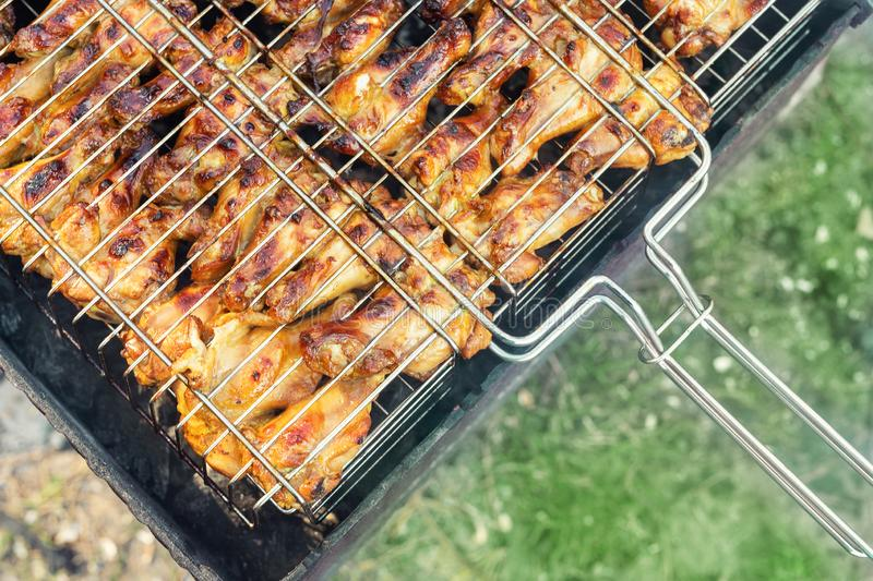 Close-up top view chicken wings cooking in metal barbecue grid on grill brazier. Outdoors weekend party on backyard. Tasty golden stock image
