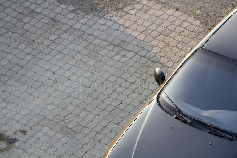 Close-up top view detail of new shiny black luxurious expensive car with dark windows parked on clean empty pavement on bright sun royalty free stock photo