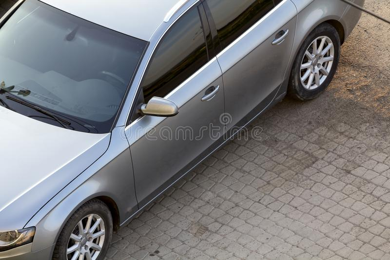 Close-up top view detail of new shiny silver luxurious expensive car parked on clean empty pavement on bright sunny day. Personal royalty free stock photography