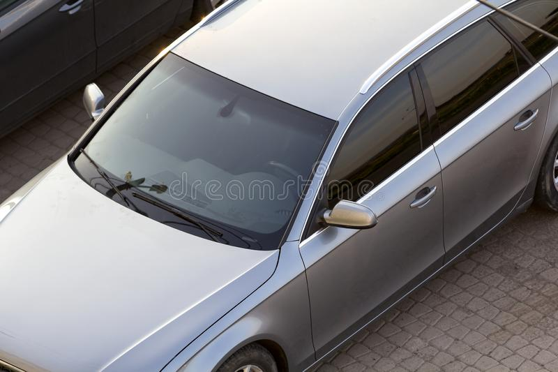 Close-up top view detail of new shiny silver luxurious expensive car parked on clean empty pavement on bright sunny day. Personal royalty free stock image
