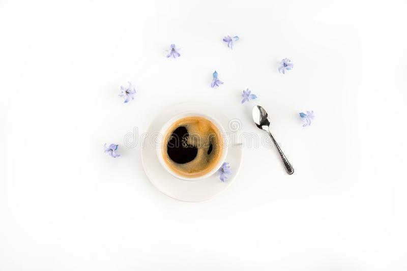 Close-up top view of fresh coffee in cup and blue hyacinth flowers royalty free stock photography