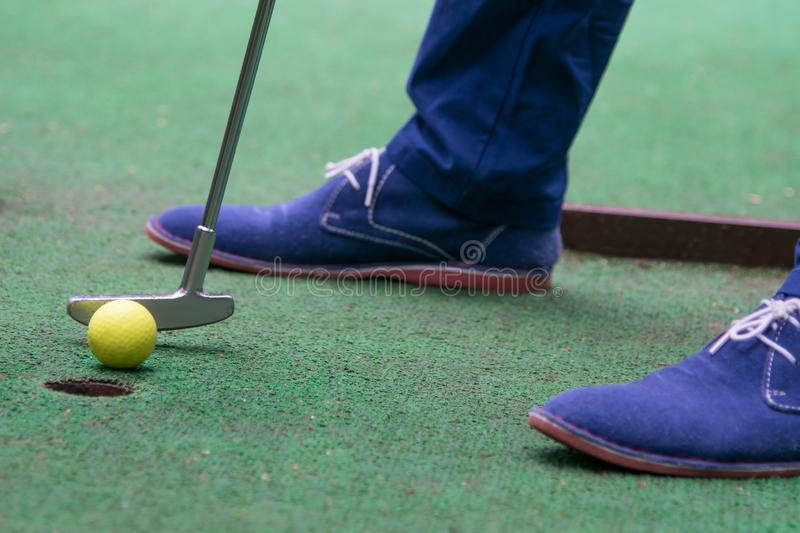 Close-up, top view on grass background, mini golf ball and blue shoes stock image