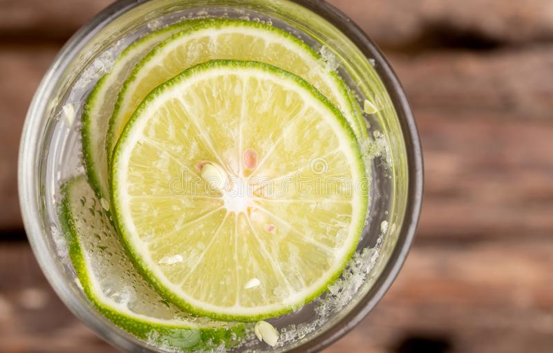 Close up top view green lime sliced in the soda water stock photo