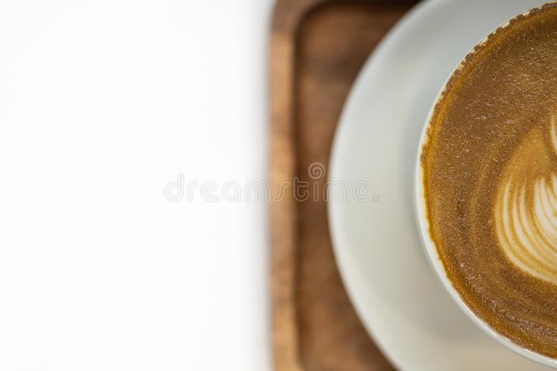 Close up top view of haft white cup of hot coffee latte with texture of milk form art and plate on wooden tray with copy space for stock photos