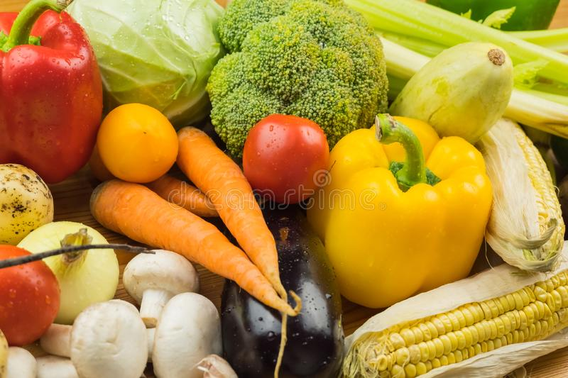 Close-up top view image of fresh organic vegetables. Locally grown bell pepper, corn, carrot, mushrooms and other natural vegan f. Ood laying on table royalty free stock image