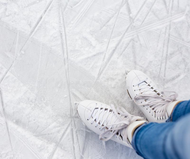 Close up top view of legs in leather skates and copy space over white scratched ice at rink royalty free stock image