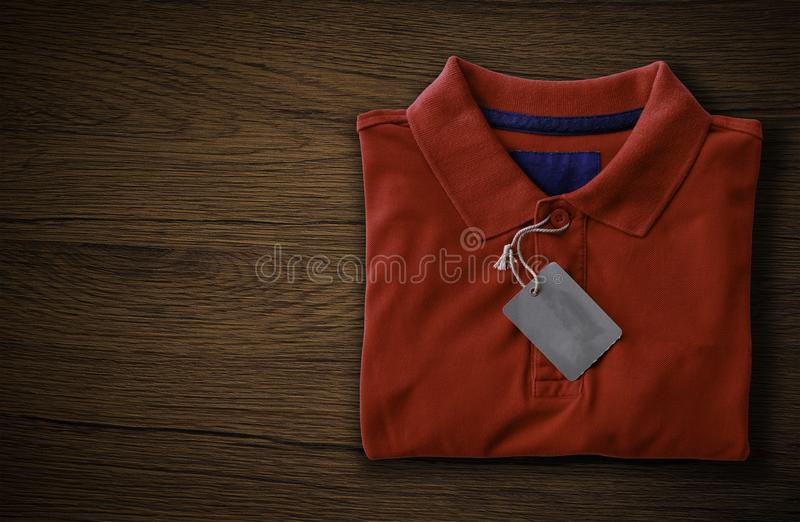 Polo shirt. Close up top view of man polo shirt put on rustic wooden table top with blank space use for texts display royalty free stock images