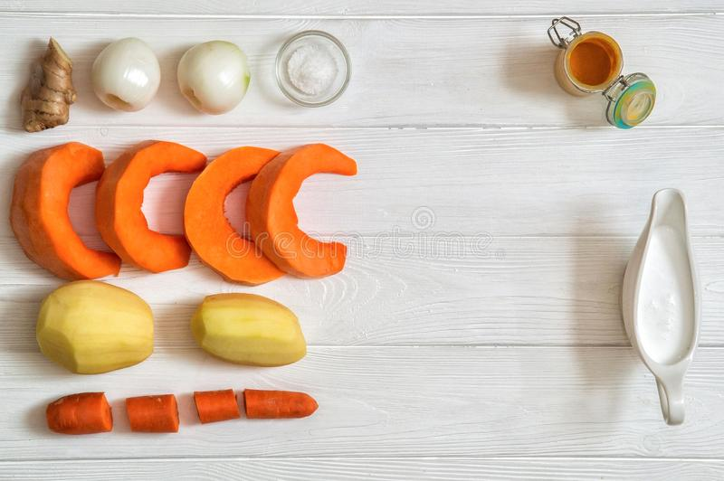 Close up, top view. Peeled lined ingredients for pumpkin cream soup: carrot, pumkin, onion, potatoes. royalty free stock photography