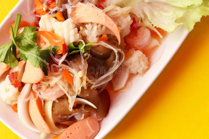 Close up top view spicy salad of vermicelli and seafood in white plate on yellow background, Thai food Yum Woon Sen stock photo