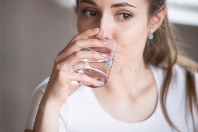 Close up top view woman drinking clear water from glass stock images