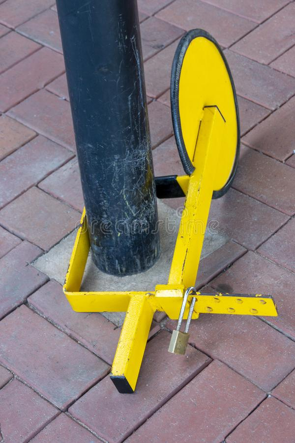 A Car Wheel Claping Device. A close up top view of a yellow and black car wheel clamping devise locked to a pole next to restricted parking area royalty free stock photos