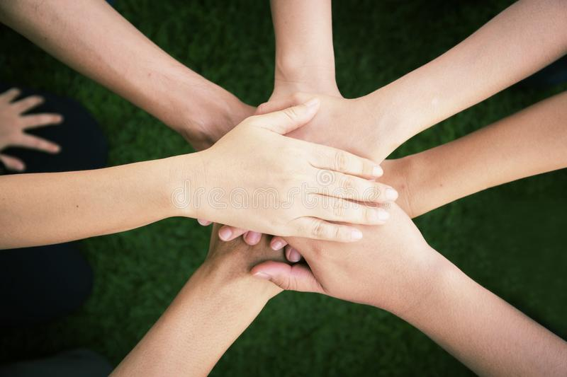 Close up top view of young people putting their hands together. stock image