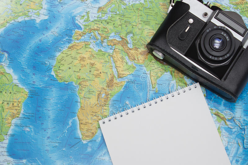 Close up of touristic map, black retro camera and notebook royalty free stock photo