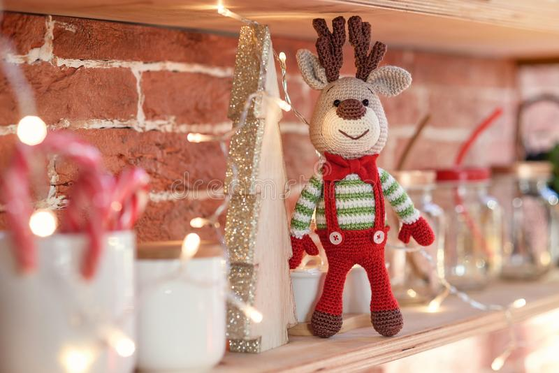 Close up toy amigurumi deer in striped sweater and stylish red butterfly tie stands on the wooden shelf royalty free stock photo