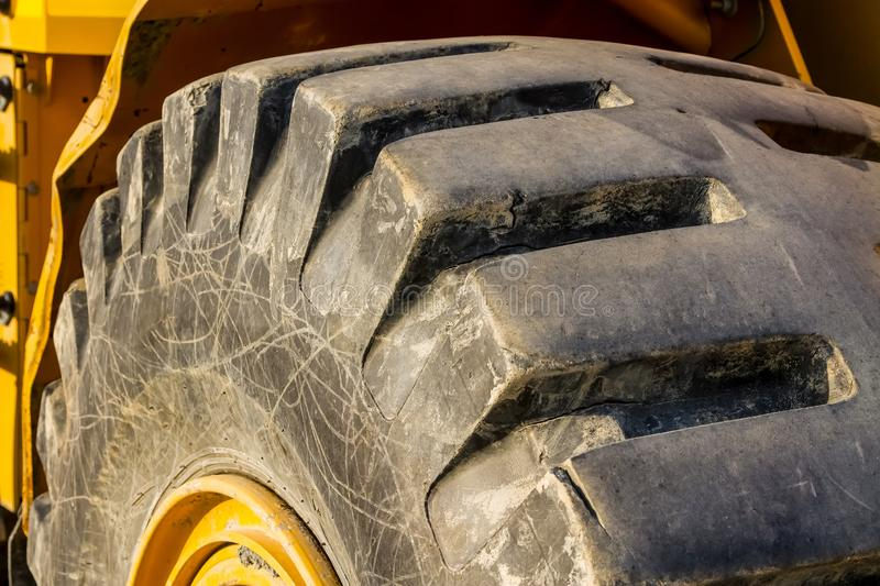 Close up of a tractor tire, Front end loader. Close up of a tractor tire, Yellow Front end loader stock photo