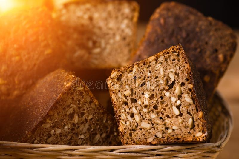 Close-up traditional artisan rye bread loaves with walnut and se. Eds on a basket in rays of the sun, selective focus stock photography
