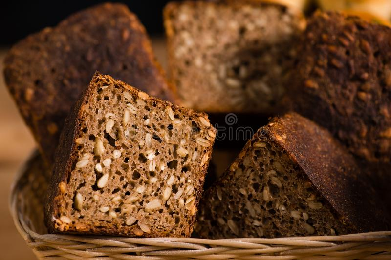 Close-up traditional artisan rye bread loaves with walnut and se. Eds on a basket, selective focus. Rustic style royalty free stock photos