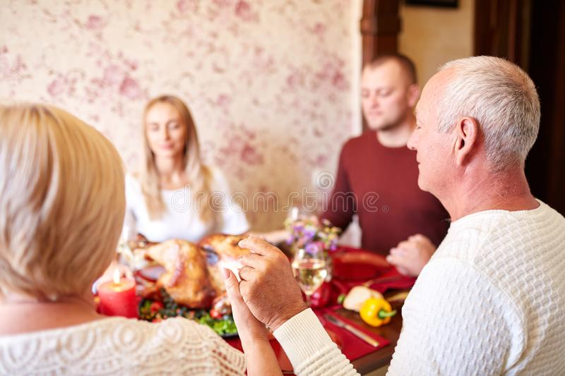 Christian family praying on a Thanksgiving dinner on a light background. Be grateful concept. stock photography