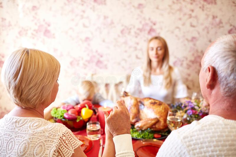 Christian family praying on a Thanksgiving dinner on a light background. Be grateful concept. Close-up of a traditional Christian family holding hands and royalty free stock photos