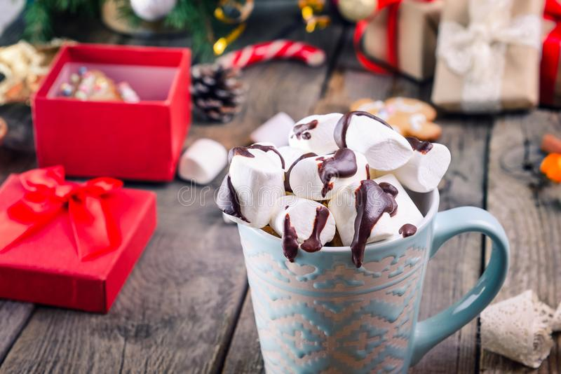 Close up Traditional hot chocolate with marshmallows and chocolate on the old rustic wooden table with christmas tree, decor. Gift boxes, cookies and spices stock images