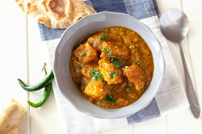 Close up traditional Indian butter chicken curry served with chapati bread in bowl. Top view royalty free stock images
