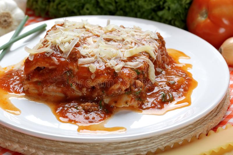 Close-up of a traditional lasagna made with minced beef bolognese sauce topped with basil leafs served on a white plate stock image