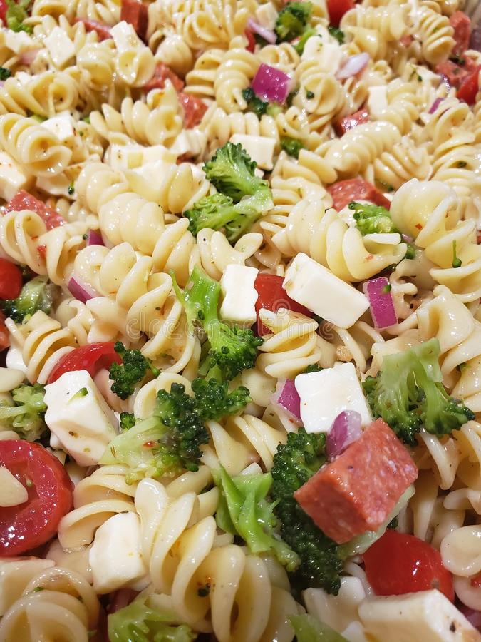 A close up of traditional pasta salad. With tomatoes, pepperoni, broccoli, pasta and cheese royalty free stock images