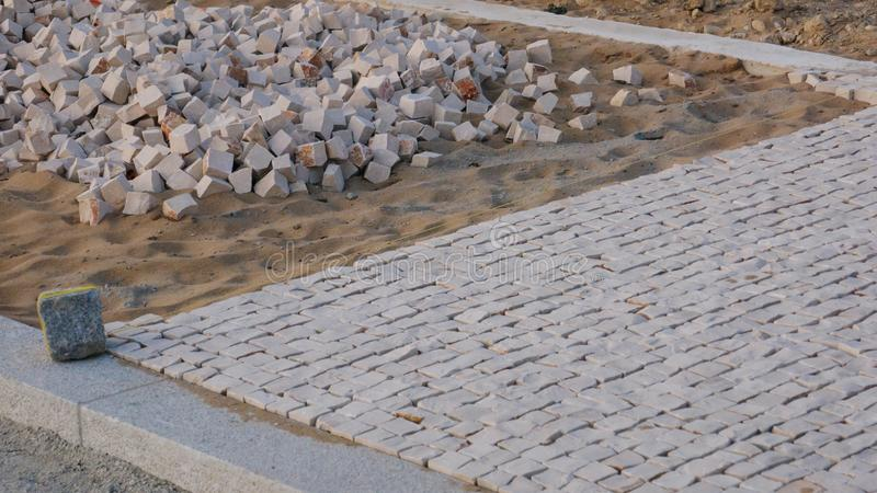 Close up of traditional Portuguese sidewalk / pavement under construction in Portugal. With loose stones in sand, and completed part on right royalty free stock photo