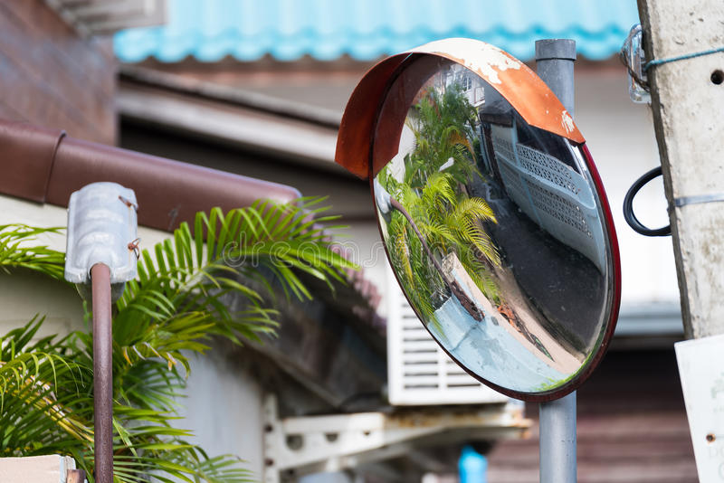 Close up traffic curve mirror at dangerous curve road with street reflection in the mirror at Koh Kret, Nonthaburi, Thailand. stock photos