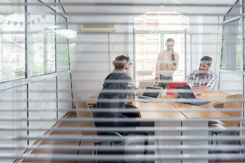 Young independent workers sharing the facilities of a modern co-working space. Close-up of the transparent interior window of an office with three young royalty free stock photos