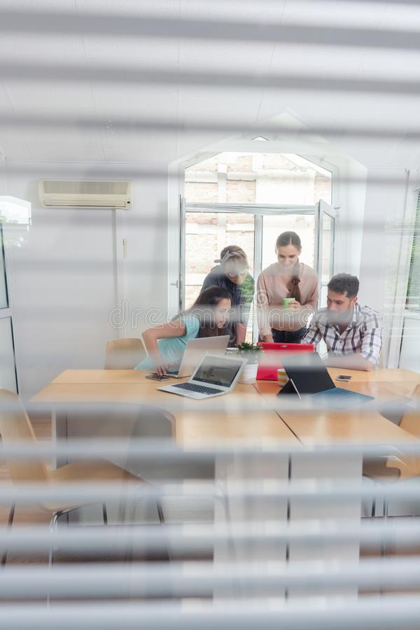 Young independent workers sharing the facilities of a modern co-working space. Close-up of the transparent interior window of an office with three young stock photo