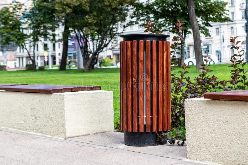 Close-up of trash cans and benches. City bench made of wood on a cement base in the Park. Space for lettering or design royalty free stock image
