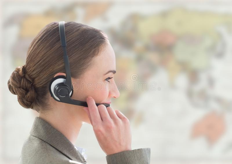 Close up of travel agent with headset against blurry map stock photo