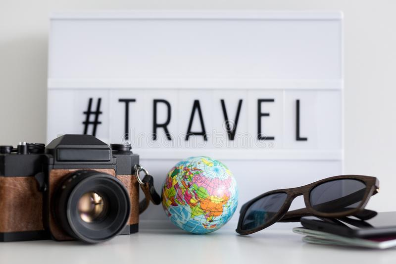 Close up of travel objects over retro light box with travel hash tag. Close up of travel objects and devices over retro light box with travel hash tag royalty free stock photos