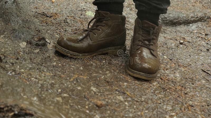 Close-up of traveler in boots standing on ground. Stock footage. Hiking boots can withstand extreme wet and muddy walk. In rainy weather royalty free stock images