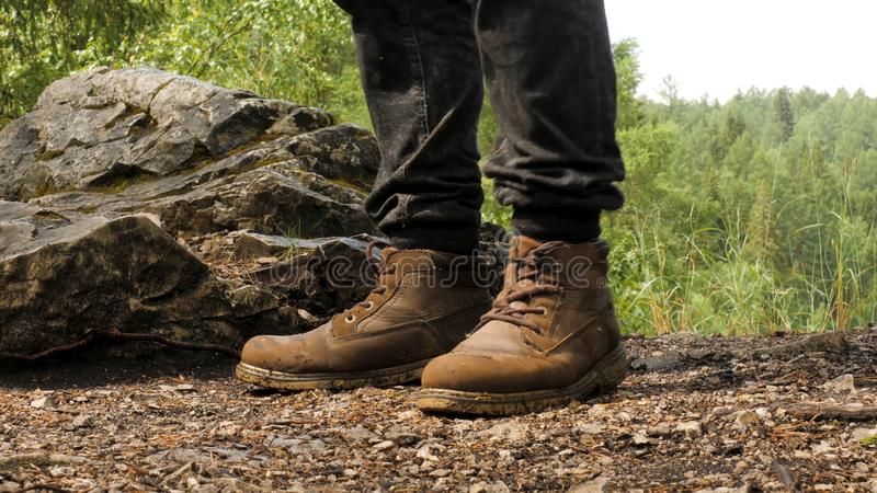 Close-up of traveler in boots standing on ground. Stock footage. Special hiking boots perfectly withstand test of mud. Long hikes and climbing mountains stock images